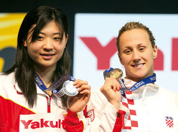 Sanja Jovanovic with the gold medal she won on the 50m backstroke at the World Championships in Manchester; Gao Chang from China took second place